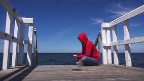 Young woman using mobile smart phone at ocean pier. Young woman using mobile smart phone at the edge of wooden ocean pier, sending sms text messages and browsing stock footage