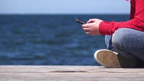 Young woman using mobile smart phone at ocean pier stock video footage