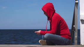 Young woman using mobile smart phone at ocean pier. Young woman using mobile smart phone at the edge of wooden ocean pier, sending sms text messages and browsing stock video footage