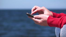 Young woman using mobile smart phone at ocean pier. Young woman using mobile smart phone at the edge of wooden ocean pier, sending sms text messages and browsing stock video