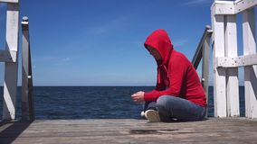 Young woman using mobile smart phone at ocean pier. Young woman using mobile smart phone at the edge of wooden ocean pier, sending sms text messages, texting stock footage