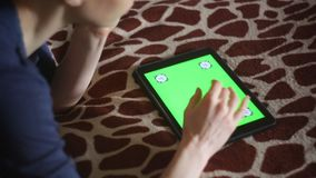 Young woman using new Apple Ipad at home. On giraffe bedcover green screen ready hands only stock video footage