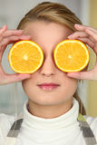 Young woman using orange halves as eyes Stock Images