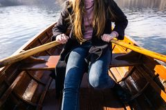 Young woman using paddle on a wooden boat - Lake Bled Slovenia rowing on wooden boats. On a sunny day stock photos