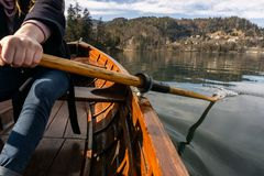 Young woman using paddle on a wooden boat - Lake Bled Slovenia rowing on wooden boats royalty free stock photography