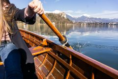 Young woman using paddle on a wooden boat with Bled Castle behind it - Lake Bled Slovenia rowing on wooden boats. Young woman using paddle on a wooden boat royalty free stock photography