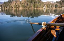 Young woman using paddle on a wooden boat - Lake Bled Slovenia rowing on wooden boats. On a sunny day royalty free stock image