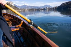 Young woman using paddle on a wooden boat with Bled Castle behind it - Lake Bled Slovenia rowing on wooden boats. Young woman using paddle on a wooden boat stock photos