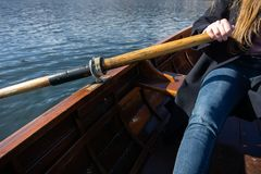 Young woman using paddle on a wooden boat - Lake Bled Slovenia rowing on wooden boats. On a sunny day stock image