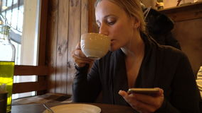Young woman using phone in a cafe. And drinking coffee stock video footage