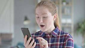Young woman using phone and feeling excited stock video footage