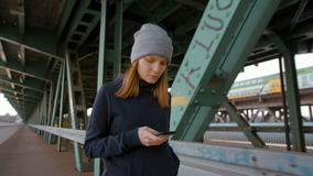 Young Woman Using Phone and Going across Industrial Bridge with Tram and Train. Young Sporty Girl is Using the Mobile Device Phone and Goes through Industrial stock video