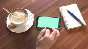 Young woman Using Phone with Green Screen In Cafe. Shot on in 4K. UHD stock footage