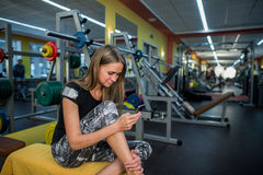 Young woman using phone in gym. Stock Image