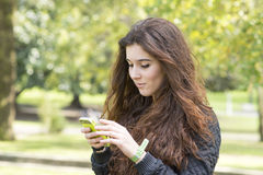 Young woman using phone, outdoor. Stock Image