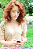 Young woman using phone. Serious young woman watching her phone while resting at park Stock Images