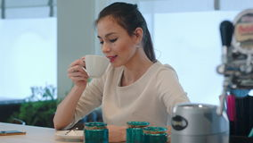 Young woman using phone while waiting for coffee at the counter. Close up shot. Professional shot on BMCC RAW with high dynamic range. You can use it e.g. in stock footage