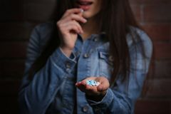 Young woman using pills for commit suicide. On brick wall background Royalty Free Stock Photo