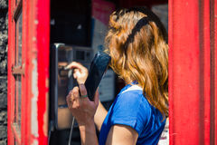 Young woman using public telephone Royalty Free Stock Photos