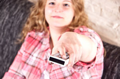 Young woman is using a remote control Stock Images