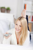 Young woman using remote control Stock Images