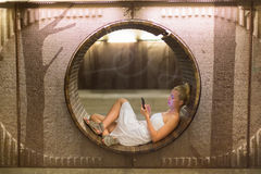 Young woman using smart phone on bench. Royalty Free Stock Images