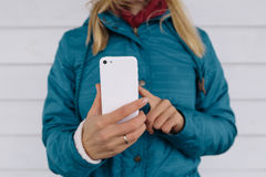 Young woman using smart phone. Woman in blue jacket uses mobile phone to take photo Stock Image