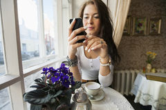 Young woman using smart phone at cafe table Royalty Free Stock Image