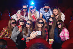 Young woman using smart phone at the cinema Stock Photos