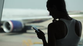 Young woman using smart phone and eating snacks at the airport. Silhouette of young woman using smart phone and eating snacks at the airport with airplane on the stock footage