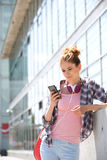 Young woman using smart phone outside office building Royalty Free Stock Photos