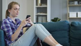 Young Woman Using Smart Phone while Relaxing on Couch royalty free stock images