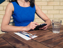 Young woman using smart phone at restaurant table Royalty Free Stock Photos