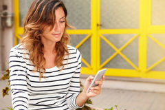Young woman using smart phone while sitting Stock Image