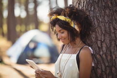 Young woman using smart phone while standing by tree trunk Royalty Free Stock Images