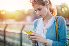 Young woman using smart phone. At sunset Royalty Free Stock Photography