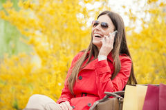 Young woman using smart phone. Woman talking on the phone and looking very happy after shopping Royalty Free Stock Image