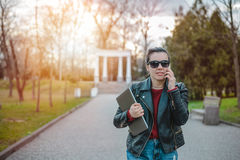 Young woman using a smart phone waling in the park. Young woman using a smart phone walking in the park with laptop in hands Royalty Free Stock Image