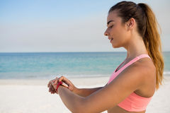 Young woman using smart watch while standing at beach Royalty Free Stock Image