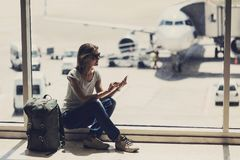 Young woman using smartphone in the airport, travel, vacations and active lifestyle concept stock image