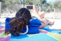 Young woman using smartphone on the beach stock photography