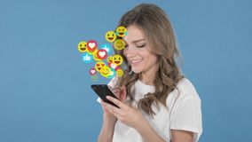 Young Woman Using Smartphone on Blue Background, Flying Smileys, Emojis and Likes