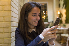 Young woman using smartphone at breakgast Royalty Free Stock Photo
