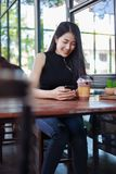 Woman using smartphone in the cafe stock image