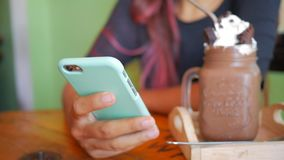 Young Woman Using Smartphone in Cafe with Sweet Chocolate Dessert on Background. stock video