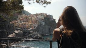 Young Tourist Woman Using Smartphone in the City Manarola Italy.