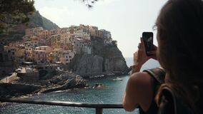 Girl using cell phone photography app in the City Manarola Italy.