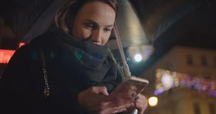 Young woman using smartphone in a city at night. Beautiful woman in the city at night holding smartphone and  texting stock video footage