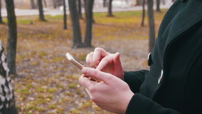 Young woman using a smartphone in the city park. A Girl holds a Mobile Phone in hands and controls finger gestures and looks at social networks stock footage