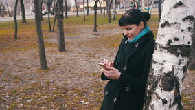 Young woman using a smartphone in the city park. A Girl holds a Mobile Phone in hands and controls finger gestures and looks at social networks stock video